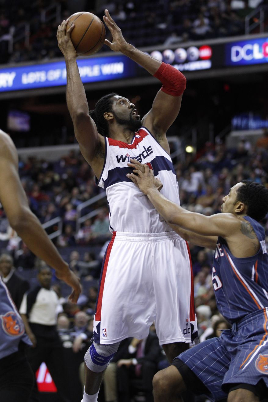 Washington Wizards center Nene, left, shoots over Charlotte Bobcats guard Gerald Henderson during the second half of an NBA game Monday, April 23, 2012, in Washington. The Wizards defeated the Bobcats 101-73. (AP Photo/Evan Vucci)