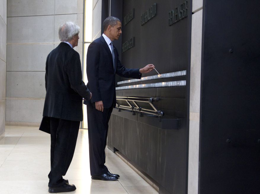 President Obama, accompanied by Elie Wiesel, a Nobel Peace Prize laureate and Holocaust survivor, lights a candle in the Hall of Remembrance as they tour the U.S. Holocaust Memorial Museum in Washington on Monday, April 23, 2012. (AP Photo/Carolyn Kaster)