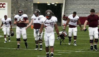 Virginia Tech's Martin Scales (25) and teammates walk across the field after their spring football game was canceled due to weather in Blacksburg, Va., on Saturday, April 21, 2012. (AP Photo/The Roanoke Times, Matt Gentry)