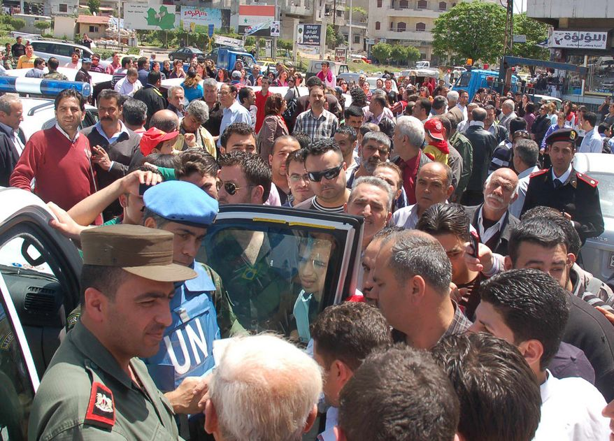 A U.N. observer and a Syrian army officer (left) listen to citizens during a visit to pro-Syrian-regime neighborhoods in Homs province of central Syria on Monday, April 23, 2012. (AP Photo/SANA)