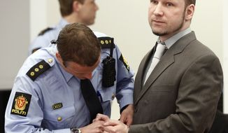 Defendant Anders Behring Breivik has his handcuffs removed as he arrives in court in Oslo on Tuesday, April 24, 2012. (AP Photo/Fredrik Varfjell, Pool)