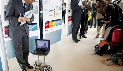 A spectator moves out of the way as Mark-Andre Duc, seen on the computer screen, directs a robot at Switzerland's Federal Institute of Technology in Lausanne, Switzerland, on Tuesday. From a hospital 162 miles away in the town of Sion, Mr. Duc imagined lifting his fingers to direct the robot. (Associated Press)