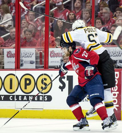 Capitals defenseman Karl Alzner played the body against Bruins left wing Benoit Pouliot as they battled for the puck during Game 4. Alzner's play is a big reason seventh-seeded Washington extended Boston to seven games in their first-round series. (Andrew Harnik/The Washington Times)