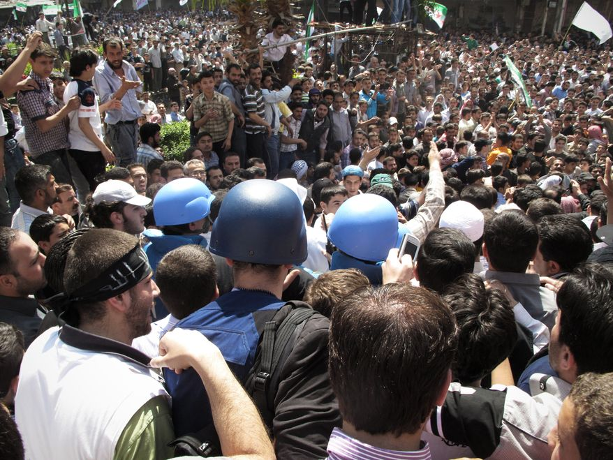 Syrian protesters gather around U.N. observers during their visit to the restive suburb of Douma, outside Damascus, Syria, on Monday, April 23, 2012. (AP Photo)