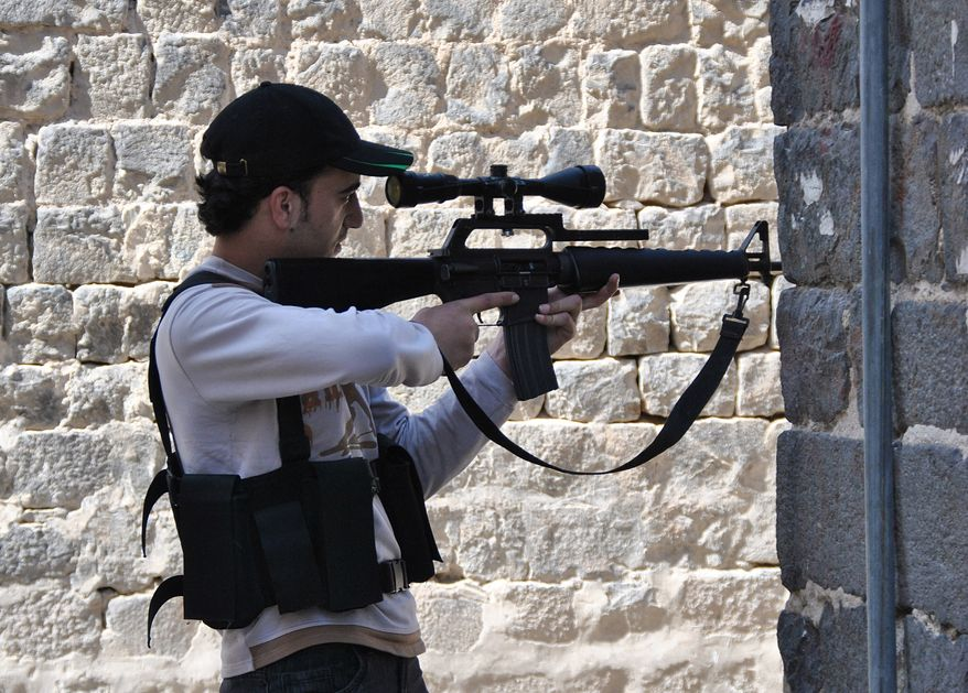 A Syrian rebel aims his gun at Khalidiyeh neighborhood in the Homs of central Syria on April 22, 2012. (Associated Press)