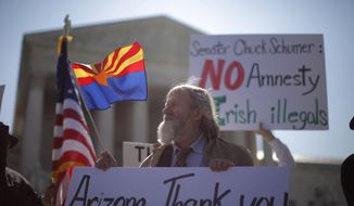 """** FILE ** Charles Balogh, from Alexandria, Va., demonstrates April 25, 2012, in front of the Supreme Court in Washington as the court holds a hearing on Arizona's """"show me your papers"""" immigration law. (Associated Press)"""