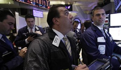** FILE ** Trader Stephen Holden (center) works with other traders at the post that handles Wal-Mart on the floor of the New York Stock Exchange on Monday, April 23, 2012. (AP Photo/Richard Drew)