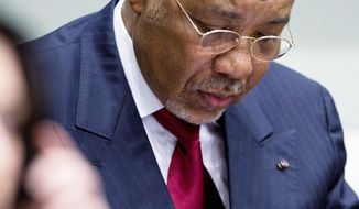 Former Liberian President Charles Taylor takes notes Thursday while awaiting a verdict in his trial for war crimes and crimes against humanity. He was found guilty of 11 charges, including terror, murder, rape and conscripting child soldiers. (Associated Press)
