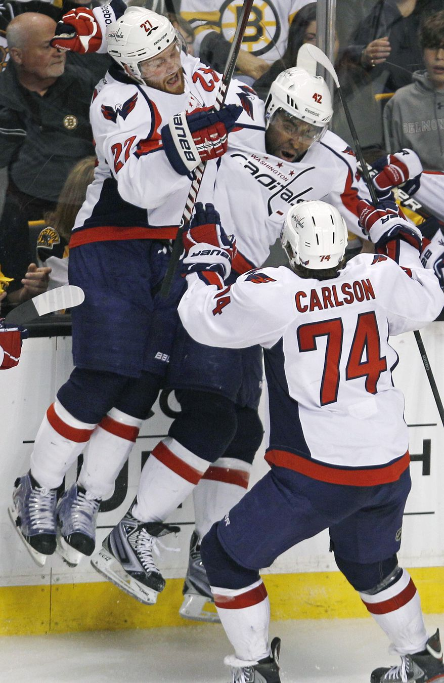 Washington Capitals right wing Joel Ward, center, is congratulated by teammates after scoring the game-winner in overtime against the Boston Bruins in Game 7 of their first-round series. (AP Photo/Charles Krupa)