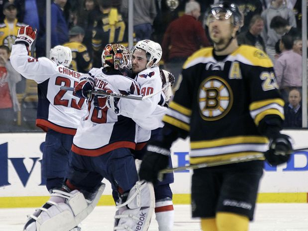 Boston Bruins center Chris Kelly (23) skates away as Washington Capitals goalie Braden Holtby (70); center Marcus Johansson (90) and left wing Jason Chimera (25) celebrate the Capitals' 2-1 win in overtime in Game 7 of the first-round playoff series, in Boston on Wednesday, April 25, 2012. (AP Photo/Elise Amendola)