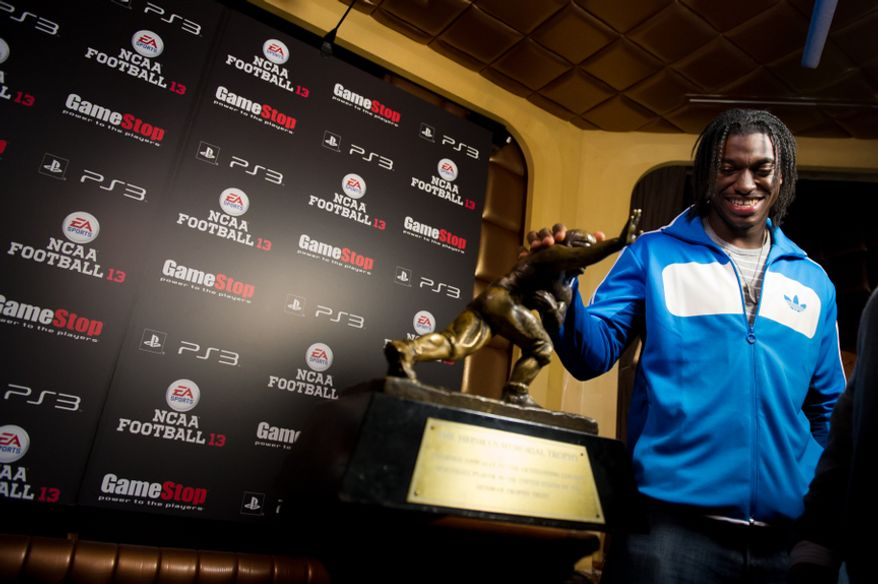 NFL bound quarterback Robert Griffin III, touches the Heisman Trophy between media interviews at the EA Sports NCAA '13 Draft Night Premiere at LAVO Nightclub in Manhattan, New York, N.Y., Tuesday, April 24, 2012. Robert Griffin III is featured on the front cover of the yet to be released NCAA Football 13 video game along side Sanders, both Heisman Trophy winners. (Andrew Harnik/The Washington Times)