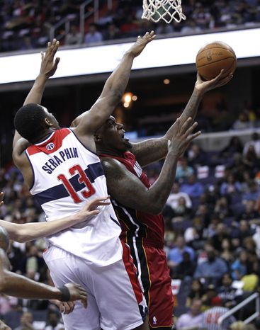 Miami Heat center Eddy Curry, right, drives to the basket against Washington Wizards forward Kevin Seraphin during the first half of an NBA basketball game on Thursday, April 26, 2012, in Washington. (AP Photo/Evan Vucci)