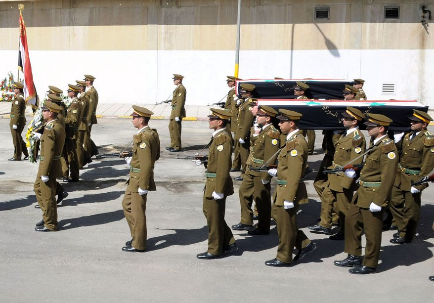 On Tuesday, April 24, 2012, a Syrian honor guard marching in a funeral procession at the military hospital in Damascus, Syria, carries the coffins of soldiers who were killed in recent violence in the country. (AP Photo/SANA)