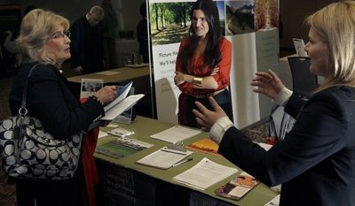 Iulia Petelea (right) and Carolina Baso (center) of International House speak with a potential applicant during a job fair in Boston on Monday, April 2, 2012. (AP Photo/Elise Amendola)