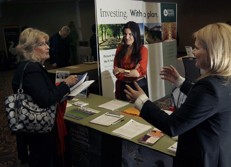 Iulia Petelea (right) and Carolina Baso (center) of International House speak with a potential applicant during a job fair in Boston on Monday, April 2, 2012. (AP Photo/Elise Amendola)