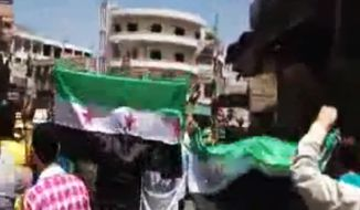 In this image made from amateur video released by Shaam News Network and accessed Thursday, April 26, 2012, a Syrian man holds the Syrian revolutionary flag during a demonstration in Hama, Syria. The Associated Press cannot independently verify the content, date, location or authenticity of this material. (AP Photo/Shaam News Network via AP video)