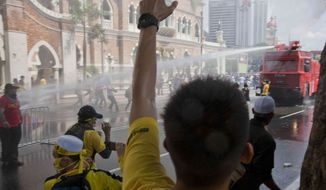 Protesters charge at a police vehicle as it sprays them with its water cannons in Kuala Lumpur, Malaysia, Saturday, April 28, 2012. (AP Photo/Mark Baker)