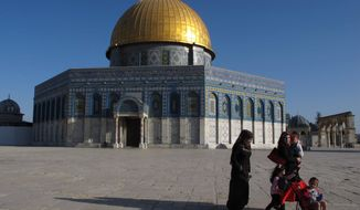 In this Wednesday, April 25, 2012, photo, a Palestinian family walks past the Dome of the Rock Mosque in the Al Aqsa Mosque compound in Jerusalem's Old City. (AP Photo/Diaa Hadid)