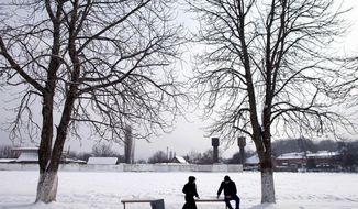 "A man and a woman on a date in the village of Serzhen-Yurt in Chechnya sit on opposite ends of a bench. Couples on dates must meet in public and sit a distance from each other. All physical contact is forbidden before marriage. Chechen President Ramzan Kadyrov supports honor killings for women with ""loose morals."" (Diana Markosian/Special to The Washington Times)"