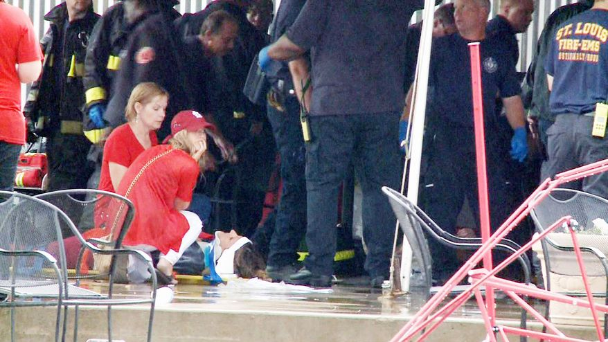 A person lies injured after high winds blew over a tent near Busch Stadium on Saturday in St. Louis. A Waterloo, Ill., man was killed, and 17 people in the tent were taken to hospitals with injuries. (Associated Press)