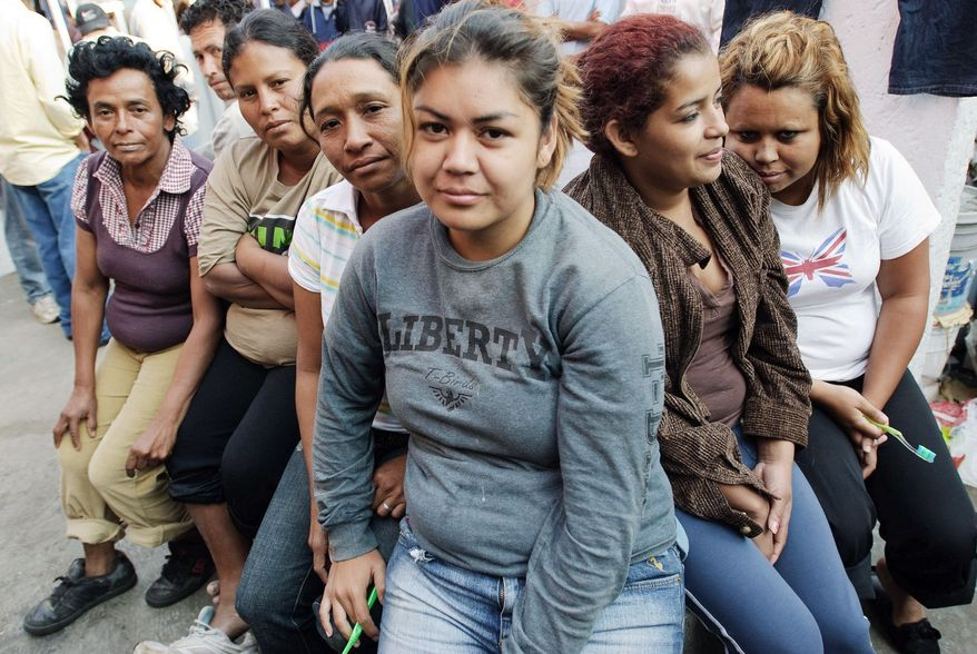 Honduran women wait for breakfast after spending the night at the migrant shelter in Tultitlan, Mexico, before resuming their journey by freight train to the U.S.