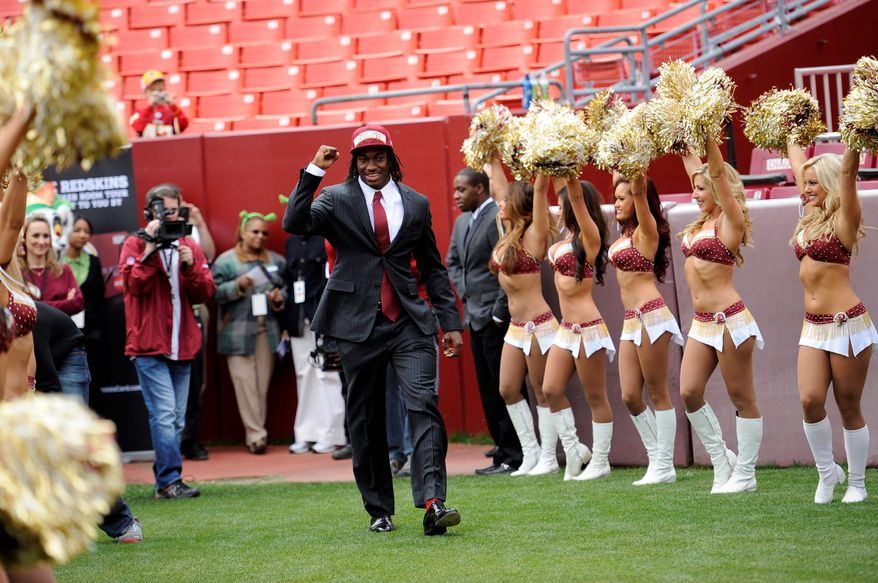 Quarterback Robert Griffin III, the second-overall draft pick by the Redskins, was cheered as he walked on the field to address fans at FedEx Field on Saturday. (Associated Press)