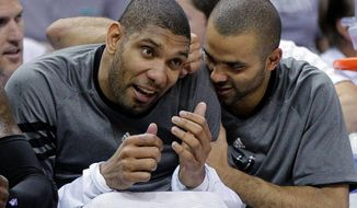San Antonio's Tony Parker (right) and Tim Duncan share a light moment during the fourth quarter of the Spurs' win over the Utah Jazz. (Associated Press)