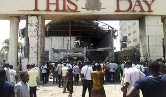 ** FILE ** People gather in front of the bombed offices of ThisDay, an influential daily newspaper, in Abuja, Nigeria, on Thursday, April. 26, 2012. (AP Photos/Gbemiga Olamikan)