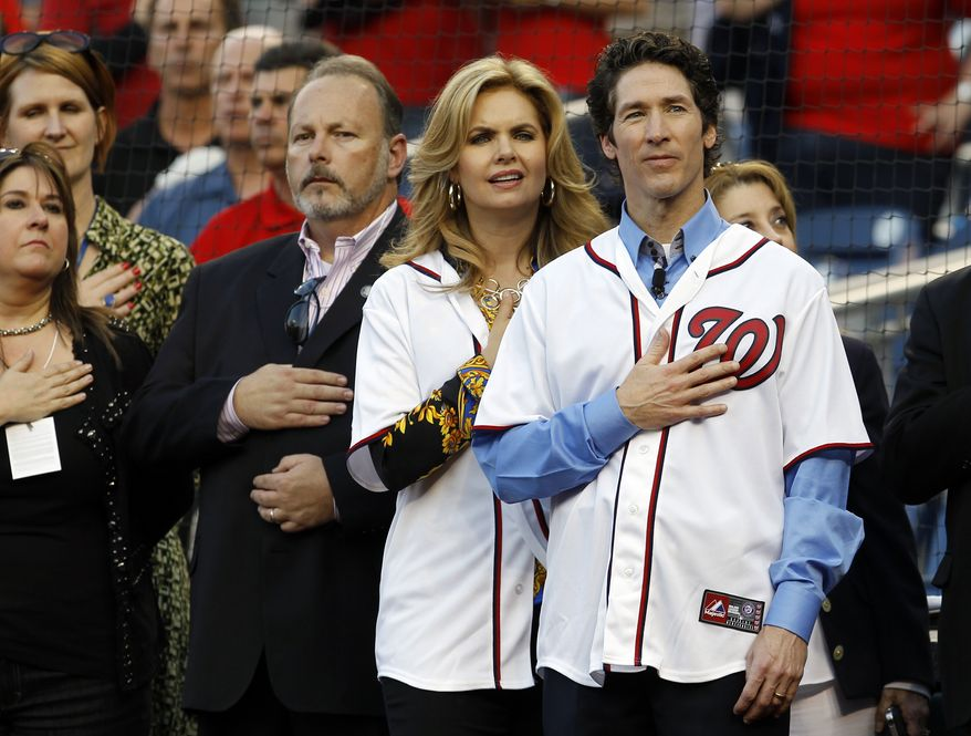 Pastor Joel Osteen of Lakewood Church, right, and his wife Victoria stand for the National Anthem prior to a Washington Nationals baseball game against the Houston Astros in Washington, Monday, April 16, 2012. (AP Photo/Ann Heisenfelt)
