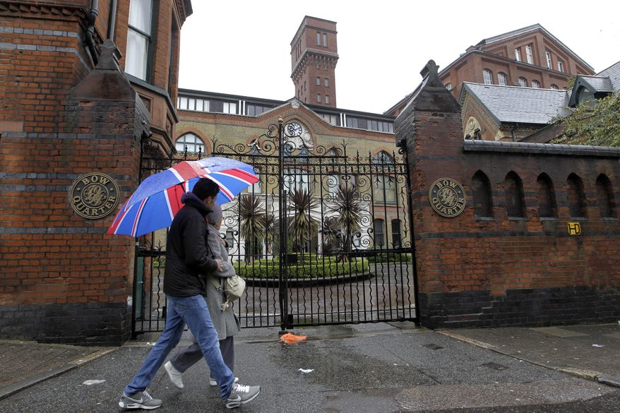 Pedestrians on Sunday, April 29, 2012, pass gated residential flats in Bow in east London, where the Defense Ministry has warned residents that surface-to-air missiles could be stationed on the rooftop during the London Olympics. (AP Photo/Sang Tan)
