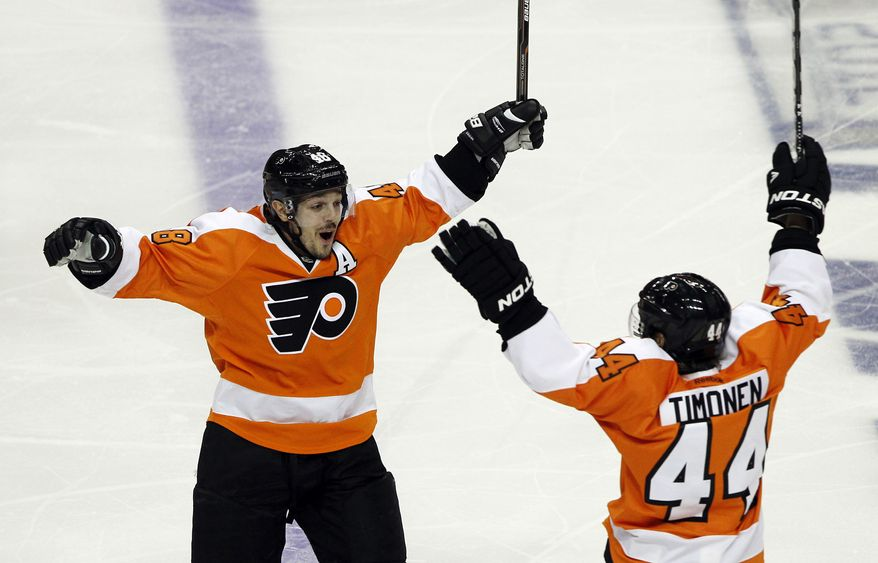 Philadelphia Flyers center Danny Briere (48) reacts with Kimmo Timonen after Briere scored the winning goal in overtime of Game 1 in a second-round NHL Stanley Cup playoff series with the New Jersey Devils, Sunday, April 29, 2012, in Philadelphia. The Flyers won 4-3. (AP Photo/Alex Brandon)