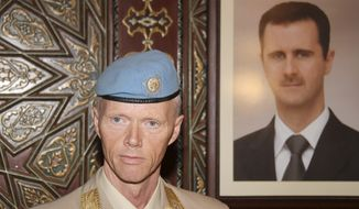 Norwegian Maj. Gen. Robert Mood, head of the U.N. observer team in Syria, is seen next to a portrait of Syrian President Bashar Assad in Damascus, Syria, on Sunday, April 29, 2012. (AP Photo/Bassem Tellawi)
