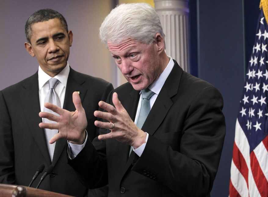 **FILE** President Obama listens to former President Bill Clinton speak Dec. 10, 2010, in the White House briefing room in Washington. (Associated Press)