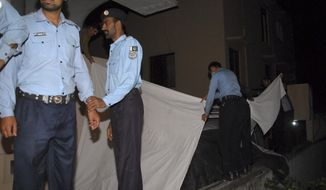 Pakistani police officers cover a vehicle to hide the family of Osama bin Laden from the media in Islamabad on Thursday, April 26, 2012. (AP Photo/M. Yasir)