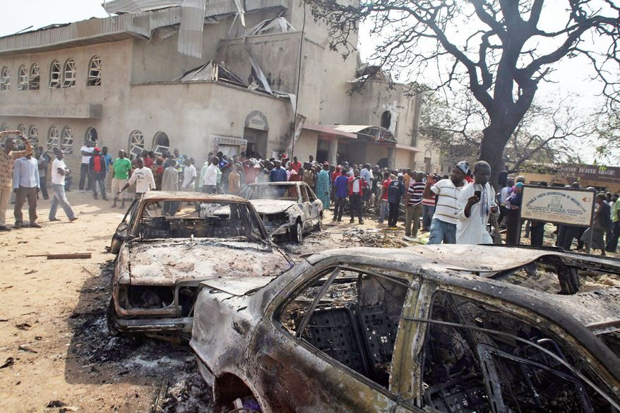Onlookers examine a destroyed car at the site of a bomb blast at St. Theresa Catholic Church in Madalla, Nigeria, on Dec. 25, 2011. An explosion ripped through the Catholic church during Christmas Mass near Nigeria's capital, killing 25. A radical Muslim sect claimed the attack and another bombing near a church in the restive city of Jos, as explosions also struck the nation's northeast. (Associated Press)