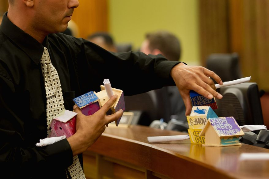 "Council chamber employee Juan Gray collects small toy homes which read, ""Kids Need Homes,"" which were placed in front of the D.C. Council by protesters who disrupt a public budget hearing at the Wilson Building to bring attention to homelessness in the District, Washington, D.C., Monday, April 30, 2012. (Andrew Harnik/The Washington Times)"