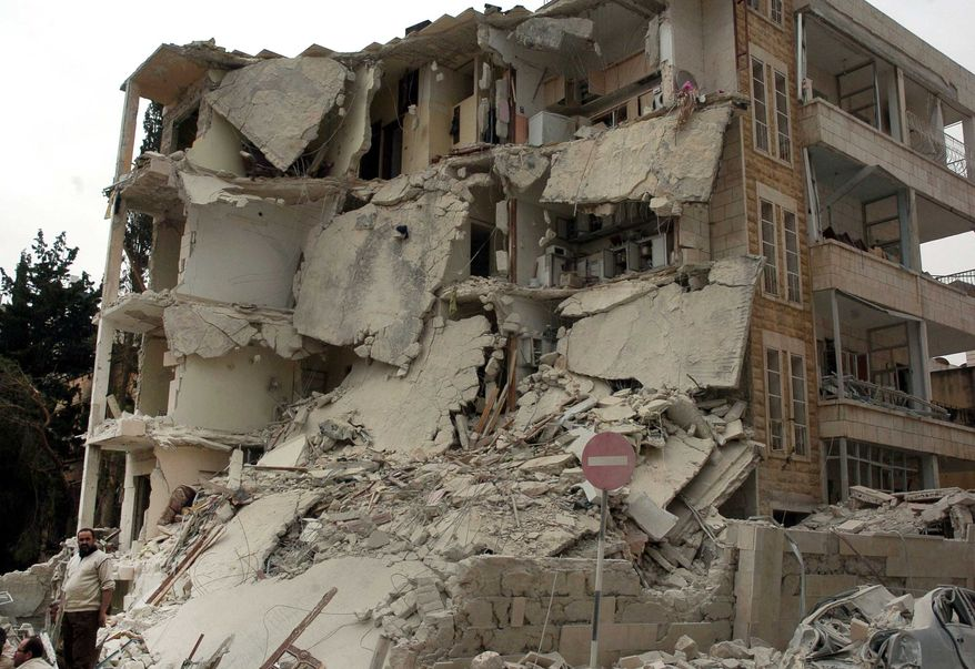 A Syrian man (left) stands in front of a building that was damaged after two bombs exploded near a military compound in Idlib, Syria, on Monday, April 30, 2012. (AP Photo/SANA)