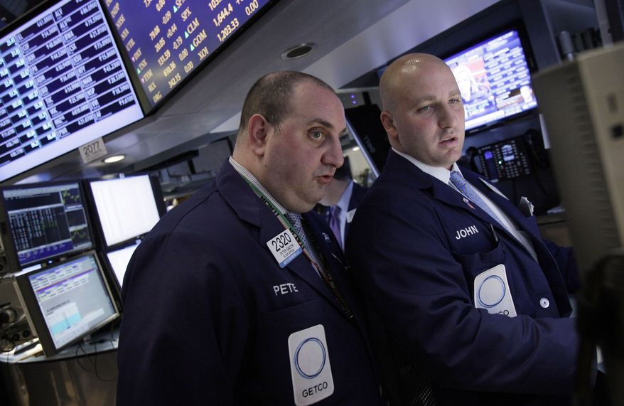** FILE ** Specialists Peter Giacchi (left) and John Parisi confer on the floor of the New York Stock Exchange on Wednesday, April 25, 2012. (AP Photo/Richard Drew)