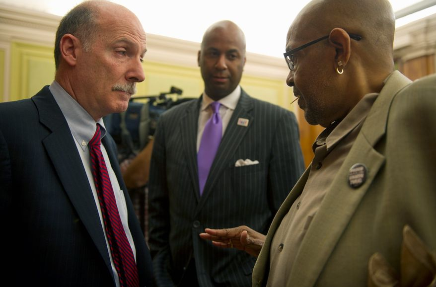 D.C. Council members Phil Mendelson (left) and Michael A. Brown (center) listen to American Federation of State, County and Municipal Employees Executive Director Geo T. Johnson's pitch for compensation for furlough days for city employees. (Barbara L. Salisbury/The Washington Times)