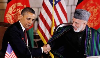At the Presidential Palace in Kabul, Afghanistan, on Wednesday, May 2, 2012, President Obama and Afghan President Hamid Karzai prepare to sign a 10-page strategic partnership agreement that will govern the U.S. support role in the Southwest Asian nation after 2014. (Associated Press)