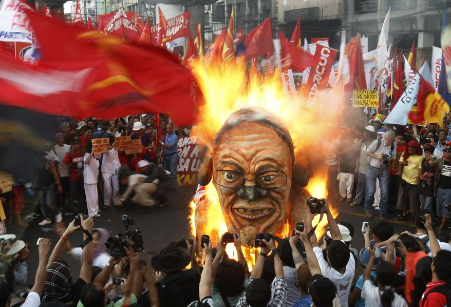 Protesters burn an effigy of Philippine President Benigno Aquino III during a rally near the president's Malacanang Palace in Manila on Labor Day, Tuesday, May 1, 2012. (AP Photo/Bullit Marquez)