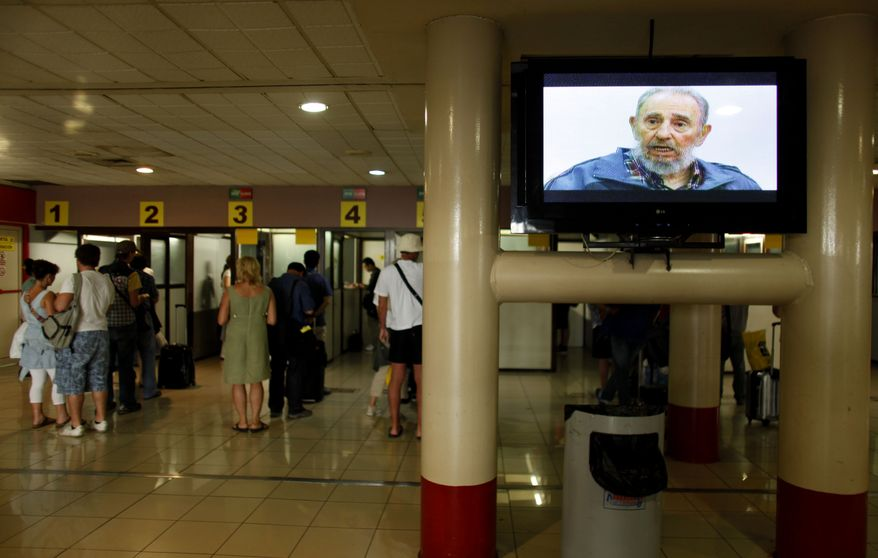 ** FILE ** Travelers line up to check with migration officials before departing from the Jose Marti International Airport in Havana, Cuba, in July 2010, while at right a TV screen displays an image of longtime Cuban leader Fidel Castro. (AP Photo/Javier Galeano, File)