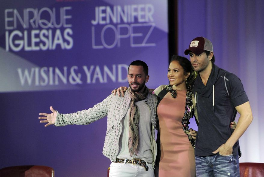Yandel, left, of the group Wisin y Yandel, Jennifer Lopez, center, and Enrique Iglesias pose together after the announcement of their summer tour together, Monday, April 30, 2012, in Los Angeles. (AP Photo/Chris Pizzello)