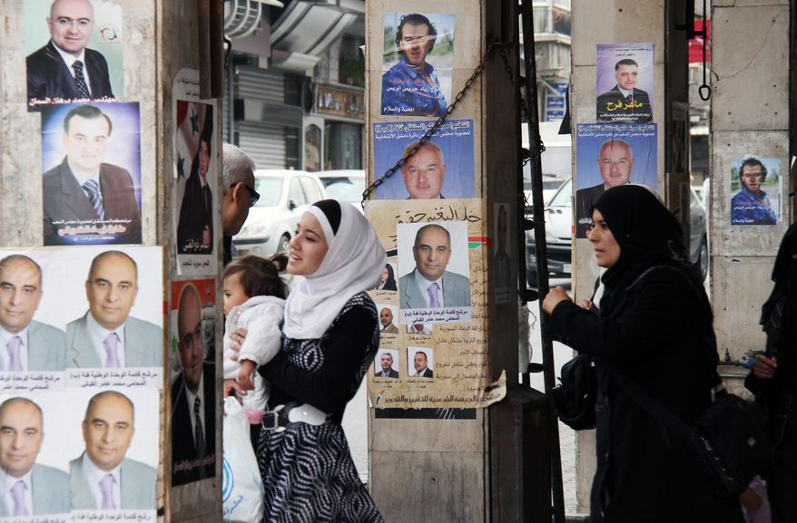 Syrians walk past posters of paramilitary candidates for the upcoming elections in Damascus, Syria, Tuesday, May 1, 2012. Preparations are under way in Syria for the parliamentary elections slated for May 7, 2012, as the crisis in the country drags on. (AP Photo Bassem Tellawi)