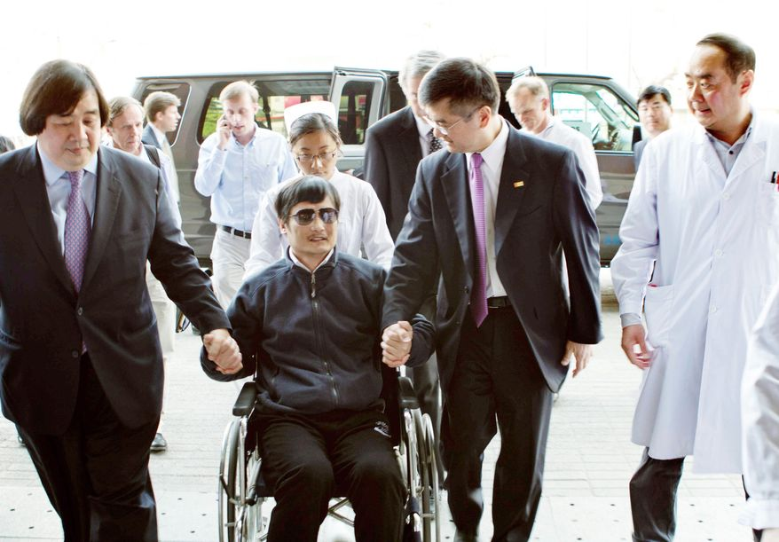 Blind lawyer Chen Guangcheng is wheeled into a hospital by U.S. Ambassador to China Gary Locke (right) in Beijing on Wednesday. State Department legal adviser Harold Koh (left) helps the Chinese activist. Mr. Chen escaped from illegal house arrest and other mistreatment in his rural town, placing himself under the protection of U.S. diplomats last week. (Associated Press)