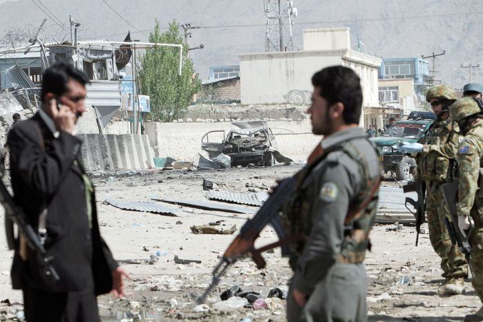 Afghan security men and NATO soldiers examine the scene of a militant attack in Kabul on Wednesday. A suicide car bomber and Taliban militants disguised in burqas attacked a compound housing hundreds of foreigners in the Afghan capital. The Taliban said the attack was a response to President Obama's surprise visit hours earlier. (Associated Press)
