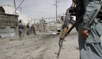 An Afghan policeman secures the area outside a compound after it was attacked by militants in Kabul, Afghanistan, on May 2, 2012. (Associated Press)