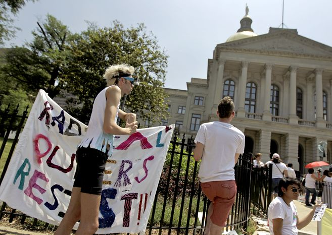 "Jesse Morgan (left) looks on during a May Day rally in Atlanta on May 1, 2012. While a black preacher told a crowd of about 100 immigration activists that incarcerated blacks and detained illegal immigrants faced similar challenges, Morgan stood to one side of the May Day protesters holding a large sign that read ""Radical Queers Resist."" (Associated Press)"
