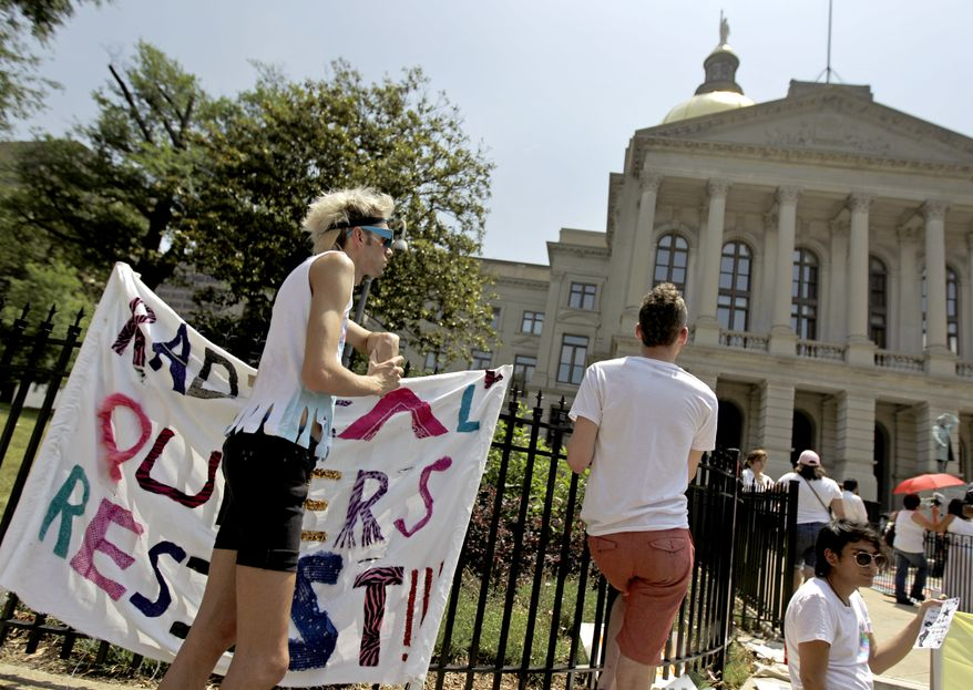 """Jesse Morgan (left) looks on during a May Day rally in Atlanta on May 1, 2012. While a black preacher told a crowd of about 100 immigration activists that incarcerated blacks and detained illegal immigrants faced similar challenges, Morgan stood to one side of the May Day protesters holding a large sign that read """"Radical Queers Resist."""" (Associated Press)"""