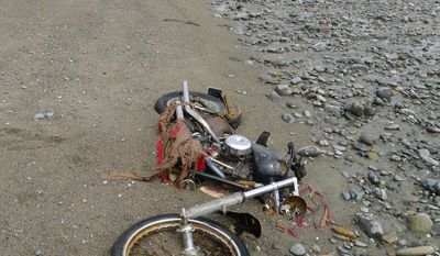 In this photo taken by Canadian Peter Mark at the end of April 2012 and released May 2, 2012, a motorbike lies on a beach in Graham Island in western Canada. Japanese media say the Harley-Davidson motorcycle lost in last year's tsunami washed up on the Canadian island about 6,400 kilometers (4,000 miles) away. (Associated Press/Kyodo News, Peter Mark)